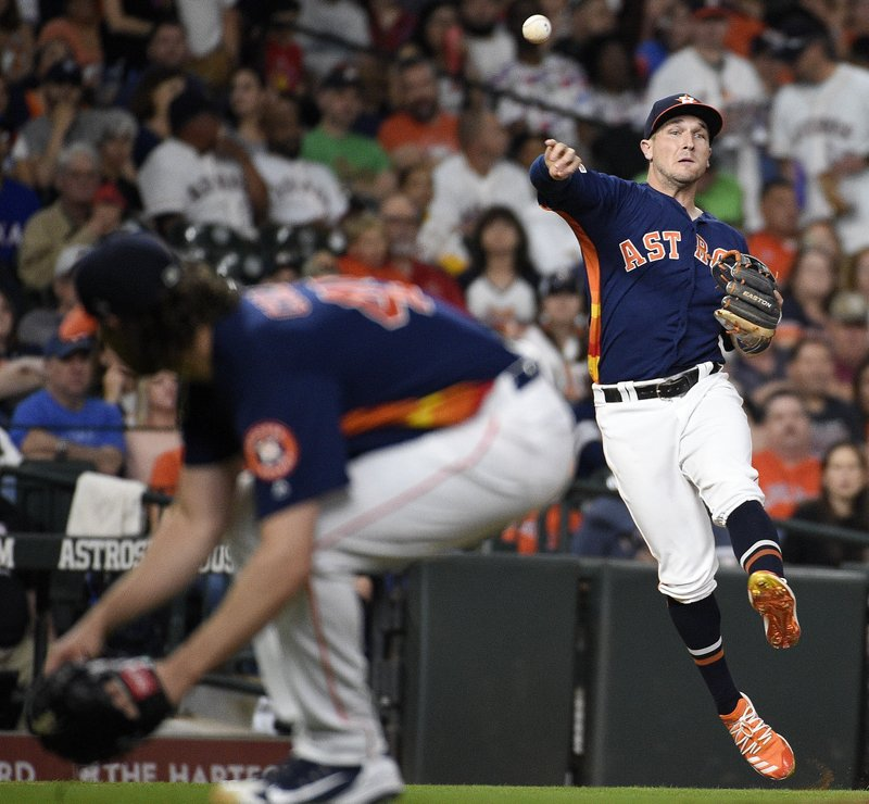 Houston Astros third baseman Alex Bregman, right, throws out Texas Rangers' Elvis Andrus as starting pitcher Gerrit Cole ducks during the fourth inning of a baseball game Saturday, May 11, 2019, in Houston. (AP Photo/Eric Christian Smith)