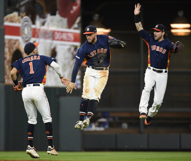 Houston Astros' Carlos Correa (1), George Springer, center, and Josh Reddick celebrates the team's 11-4 win over the Texas Rangers in a baseball game, Saturday, May 11, 2019, in Houston. (AP Photo/Eric Christian Smith)