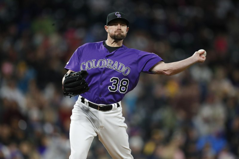 Colorado Rockies relief pitcher Mike Dunn throws to first base to keep San Diego Padres' Austin Hedges close to the bag during the seventh inning of a baseball game Saturday, May 11, 2019, in Denver. (AP Photo/David Zalubowski)