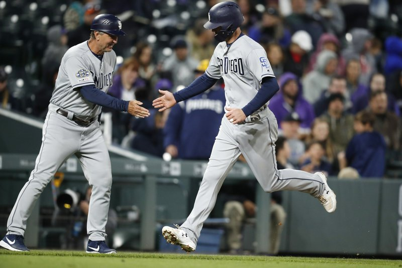 San Diego Padres third base coach Glenn Hoffman, left, congratulates Wil Myers on his solo home run off Colorado Rockies starting pitcher Jon Gray during the seventh inning of a baseball game Saturday, May 11, 2019, in Denver. (AP Photo/David Zalubowski)