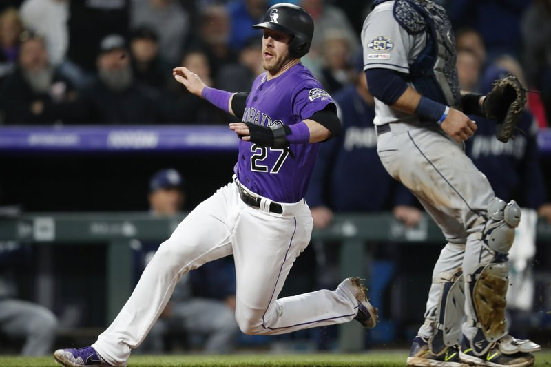 Colorado Rockies' Trevor Story, left, scores on a sacrifice fly by Nolan Arenado as San Diego Padres catcher Austin Hedges waits for the throw during the sixth inning of a baseball game Saturday, May 11, 2019, in Denver. (AP Photo/David Zalubowski)