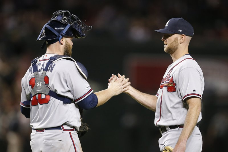 Atlanta Braves pitcher Jonny Venters and catcher Brian McCann celebrate after defeating the Arizona Diamondbacks in a baseball game, Saturday, May 11, 2019, in Phoenix. (AP Photo/Rick Scuteri)