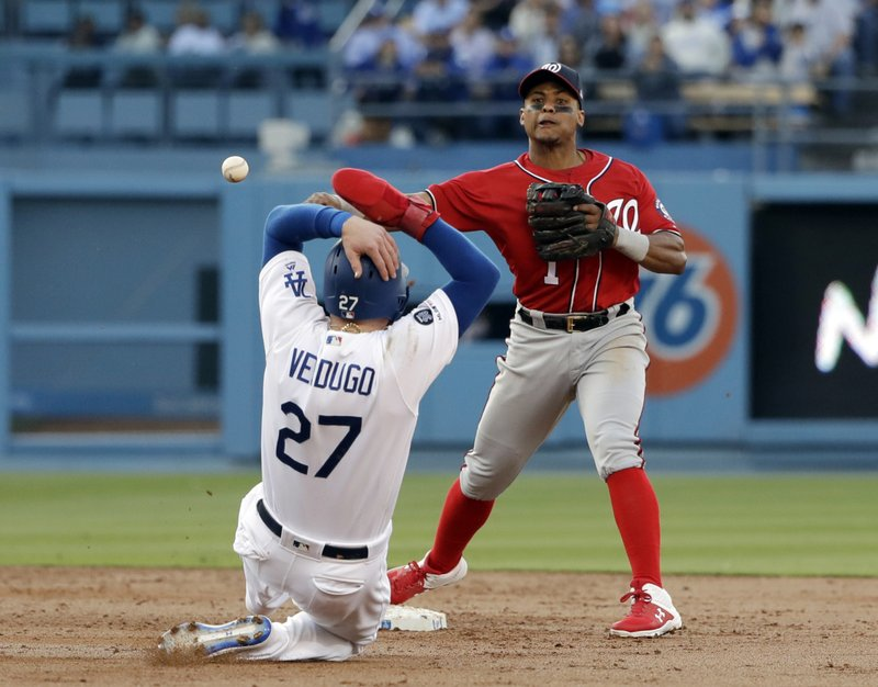 Washington Nationals shortstop Wilmer Difo, top, completes a double play over Los Angeles Dodgers' Alex Verdugo (27) on ground ball from Enrique Hernandez during the second inning of a baseball game Saturday, May 11, 2019, in Los Angeles. (AP Photo/Marcio Jose Sanchez)