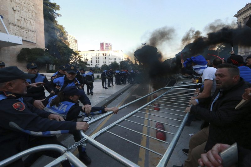 Protesters try to remove a metal fence during clashes with police outside the Government building in Tirana, Saturday, May 11, 2019. (AP Photo/Hektor Pustina)