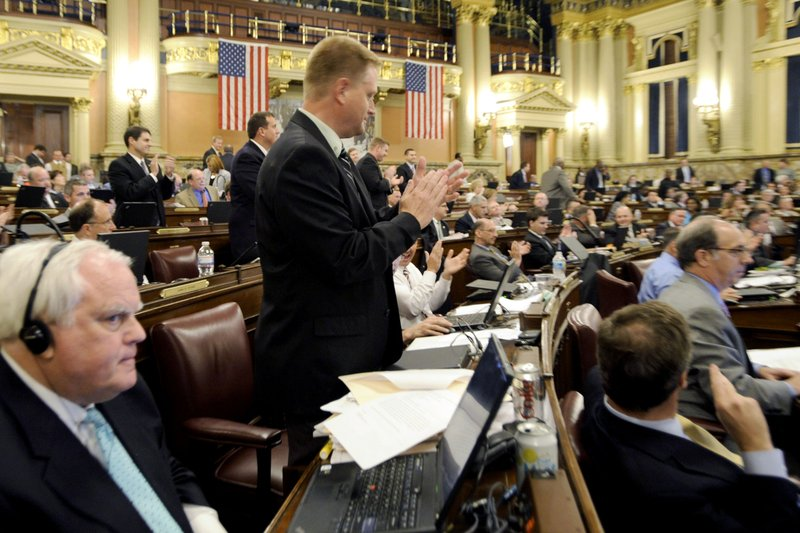 FILE - In this June 29, 2011, file photo  file photo Rep. Fred Keller, standing center, applauds after the floor of the House the vote on passing the 2011-2012 Pennsylvania state budget in Harrisburg, Pa. (AP Photo/Bradley C. Bower, File)