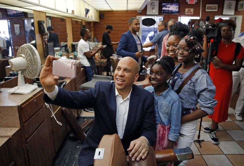 FILE - In this April 20, 2019 photo, Democratic presidential candidate Sen. Cory Booker Democratic takes a selfie with people at a barber shop during a campaign stop in Las Vegas. (AP Photo/John Locher, File)
