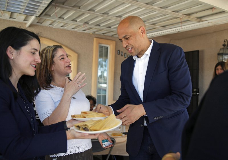 FILE - In this April 20, 2019 photo, Democratic presidential candidate Sen. Cory Booker eats a tamale while visiting a home in Las Vegas. (AP Photo/John Locher, File)