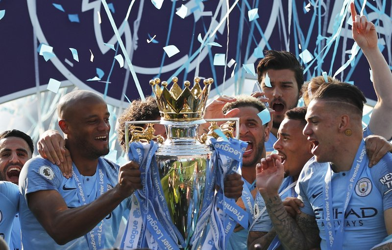 Manchester City's Vincent Kompany lifts the English Premier League trophy after the English Premier League soccer match between Brighton and Manchester City at the AMEX Stadium in Brighton, England, Sunday, May 12, 2019. (AP Photo/Frank Augstein)
