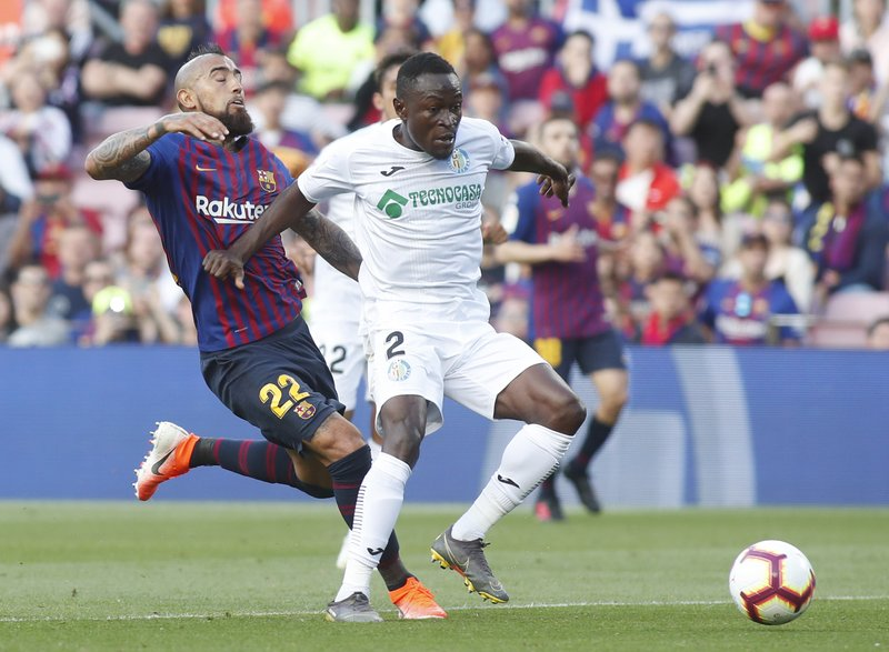 Barcelona midfielder Arturo Vidal fights for the ball against Getafe's Djene Dakonam during the Spanish La Liga soccer match between FC Barcelona and Getafe at the Camp Nou stadium in Barcelona, Spain, Sunday, May 12, 2019. (AP Photo)