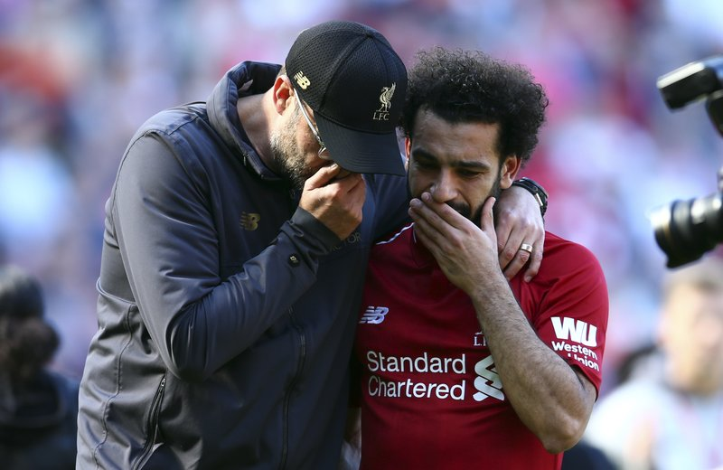 Liverpool manager Juergen Klopp, left, talks to Liverpool's Mohamed Salah at the end of the English Premier League soccer match between Liverpool and Wolverhampton Wanderers at the Anfield stadium in Liverpool, England, Sunday, May 12, 2019. (AP Photo/Dave Thompson)