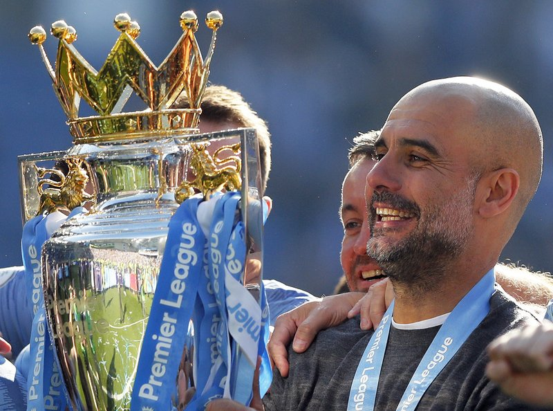 Manchester City coach Pep Guardiola lifts the English Premier League trophy after the English Premier League soccer match between Brighton and Manchester City at the AMEX Stadium in Brighton, England, Sunday, May 12, 2019. (AP Photo/Frank Augstein)