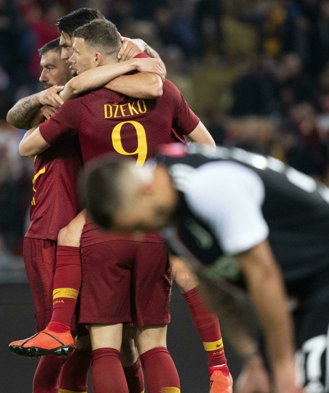 Romas Edin Dzeko, center, jubilates with his teammates Romas Cengiz Under after scoring the 2-0 goal during Serie A soccer match as Roma - FC Juventus at Olimpico Stadium in Rome, Sunday, May 12, 2019. (Claudio Peri/ANSA via AP)