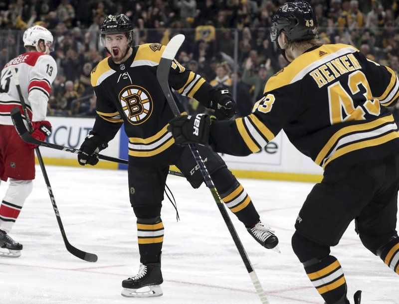 Boston Bruins' Connor Clifton, center, celebrates his goal against the Carolina Hurricanes with teammate Danton Heinen (43) during the second period in Game 2 of the NHL hockey Stanley Cup Eastern Conference final series, Sunday, May 12, 2019, in Boston. (AP Photo/Charles Krupa)