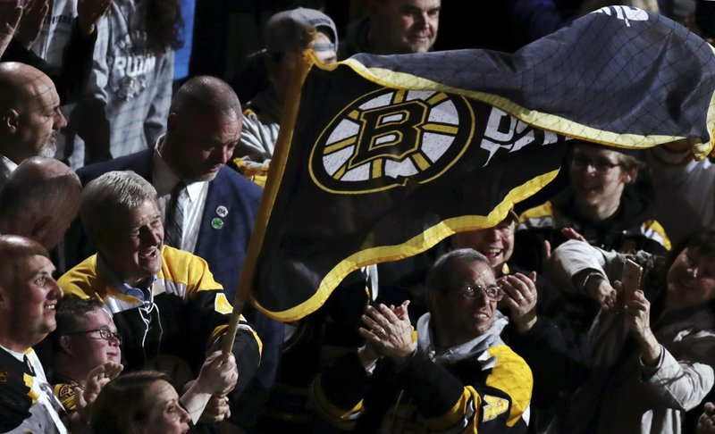 Boston Bruins great Bobby Orr, left, smiles as he waves a team flag with fans prior to Game 2 of the NHL hockey Stanley Cup Eastern Conference final against the Carolina Hurricanes, Sunday, May 12, 2019 in Boston. (AP Photo/Charles Krupa)