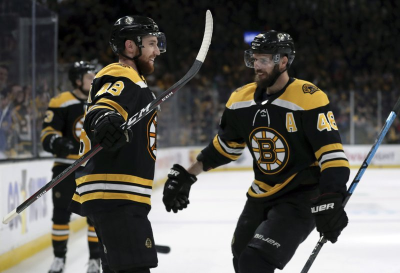 Boston Bruins' Matt Grzelcyk, left, celebrates his goal against the Carolina Hurricanes with David Krejci during the second period in Game 2 of the NHL hockey Stanley Cup Eastern Conference final series, Sunday, May 12, 2019, in Boston. (AP Photo/Charles Krupa)