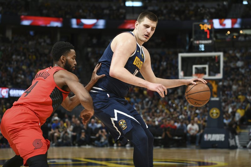 Denver Nuggets center Nikola Jokic, right, works the ball inside to the rim as Portland Trail Blazers forward Maurice Harkless defends in the first half of Game 7 of an NBA basketball second-round playoff series Sunday, May 12, 2019, in Denver. (AP Photo/John Leyba)