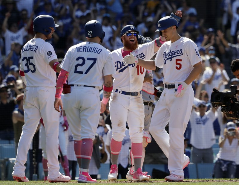 Los Angeles Dodgers' Corey Seager (5) is met at home plate by teammates Cody Bellinger (35), Alex Verdugo (27) and Justin Turner (10) after Seager's grand-slam home run against the Washington Nationals during the eighth inning of a baseball game Sunday, May 12, 2019, in Los Angeles. (AP Photo/Marcio Jose Sanchez)