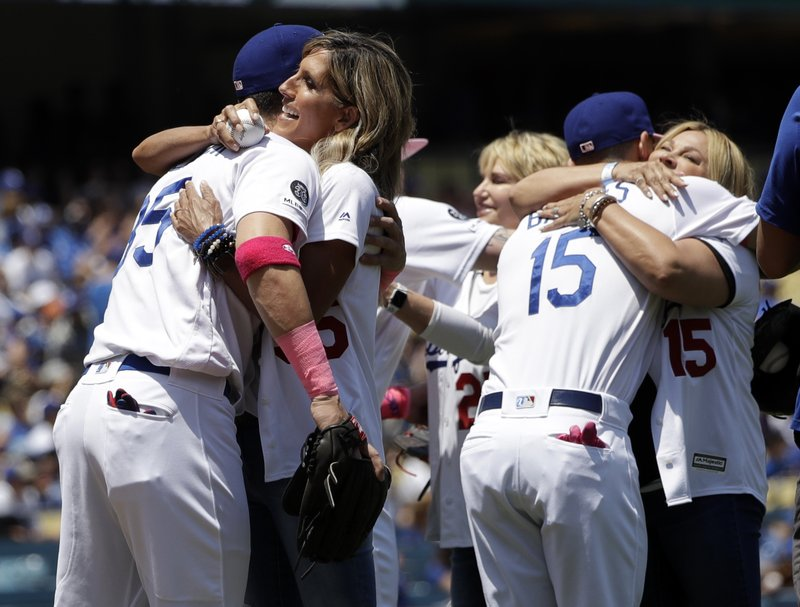 Los Angeles Dodgers' Cody Bellinger, left, hugs his mother Jennifer and Austin Barnes (15) hugs his mother Stephanie after the mothers threw ceremonial first pitches before a baseball game against the Washington Nationals, Sunday, May 12, 2019, in Los Angeles. (AP Photo/Marcio Jose Sanchez)