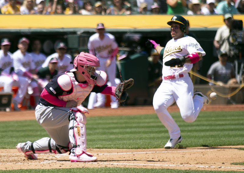 Oakland Athletics' Ramon Laureano (22) scores from second base on Stephen Piscotty's RBI single as Cleveland Indians catcher Roberto Perez (55) awaits the tardy relay during the third inning of a baseball game, Sunday, May 12, 2019, in Oakland, Calif. (AP Photo/D. Ross Cameron)