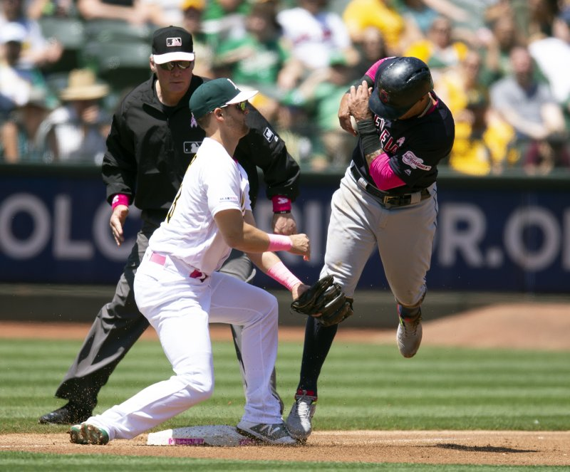 Oakland Athletics third baseman Chad Pinder (18) puts the tag on Cleveland Indians Leonys Martin as he attempts to steal third base during the second inning of a baseball game, Sunday, May 12, 2018, in Oakland, Calif. (AP Photo/D. Ross Cameron)