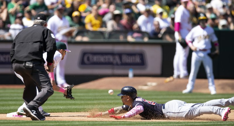 Cleveland Indians' Carlos Gonzalez (24) slides safely into third base ahead of the relay to Oakland Athletics third baseman Chad Pinder (18) as he goes from first to third on a single by Jordan Luplow during the sixth inning of a baseball game, Sunday, May 12, 2019, in Oakland, Calif. (AP Photo/D. Ross Cameron)