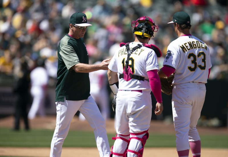 Oakland Athletics manager Bob Melvin, left, takes the ball from starting pitcher Daniel Mengden (33) during a pitching change in the sixth inning of a baseball game against the Cleveland Indians, Sunday, May 12, 2019, in Oakland, Calif. (AP Photo/D. Ross Cameron)