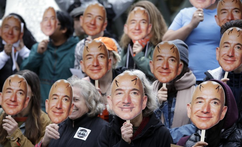 FILE - In this Oct. 31, 2018, file photo, demonstrators hold images of Amazon CEO Jeff Bezos near their faces during a Halloween-themed protest at Amazon headquarters over the company's facial recognition system,