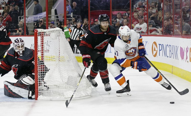 Carolina Hurricanes goalie Curtis McElhinney and Jaccob Slavin (74) defend against New York Islanders' Jordan Eberle (7) during the second period of Game 4 of an NHL hockey second-round playoff series in Raleigh, N. (AP Photo/Gerry Broome)