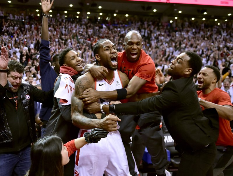 Toronto Raptors forward Kawhi Leonard, center, celebrates his game-winning basket as time expired at the end of an NBA Eastern Conference semifinal basketball game against the Philadelphia 76ers, in Toronto on Sunday, May 12, 2019. (Frank Gunn/The Canadian Press via AP)