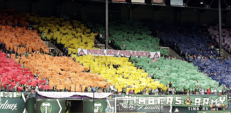 FILE - In this May 12, 2013, photo Portland Timbers fans hold up a multitude of different colored pieces of cloth and a banner sign as a display against homophobia before their MLS soccer game against Chivas USA in Portland, Ore. (AP Photo/Don Ryan)