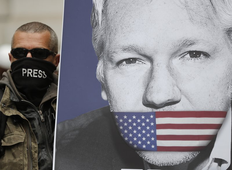 A supporter of Julian Assange, with a poster of the WikiLeaks founder, joins other protesters to block a major road in front of Westminster Magistrates Court in London, Thursday, May 2, 2019. (AP Photo/Frank Augstein)
