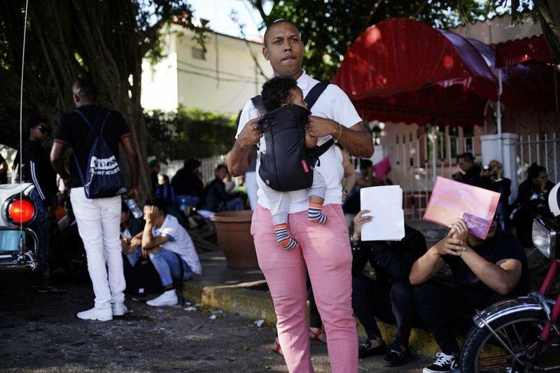 In this April 26, 2019, photo, a man holds his baby while he waits his turn to enter Nicaragua's embassy to apply for travel visas for him and his son to Nicaragua, in Havana, Cuba. (AP Photo/Ramon Espinosa)