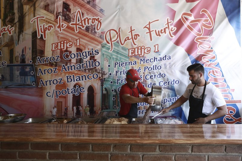 In this April 25, 2019 photo, Cuban migrant Danil Hernandez, right, prepares to serve up traditional Cuban food to customers at Little Habana restaurant in Ciudad Juarez, Mexico. (AP Photo/Christian Torres)