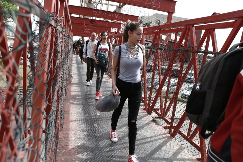 In this April 29, 2019, photo, Cuban migrants are escorted by Mexican immigration officials in Ciudad Juarez, Mexico, as they cross the Paso del Norte International bridge to be processed as asylum seekers on the U. (AP Photo/Christian Torres)