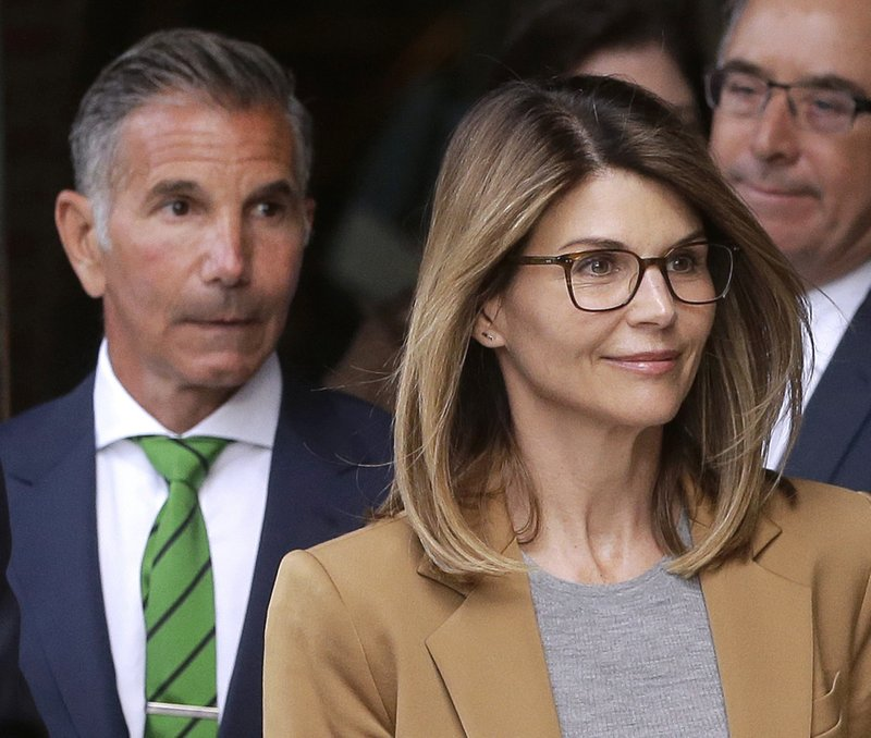 FILE - In this April 3, 2019 file photo, actress Lori Loughlin, front, and husband, clothing designer Mossimo Giannulli, left, depart federal court in Boston after facing charges in a nationwide college admissions bribery scandal. (AP Photo/Steven Senne, File)