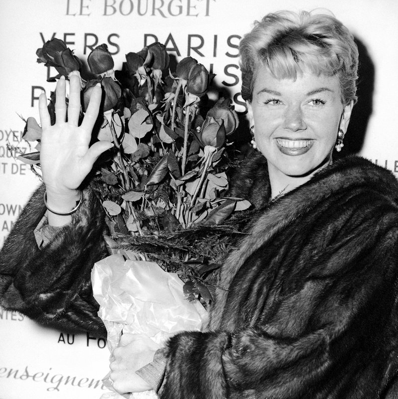 FILE - In this April 15, 1955 file photo, American actress and singer Doris Day holds a bouquet of roses at Le Bourget Airport in Paris, France after flying in from London. (AP Photo, File)