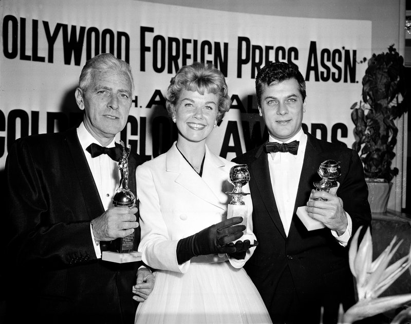 FILE - In this Feb. 26, 1958 file photo, actress Doris Day, center, Tony Curtis, right, and Buddy Adler pose with their awards presented to them by the Hollywood Foreign Press Association at its annual awards dinner in the Cocoanut Grove in Los Angeles. (AP Photo, File)