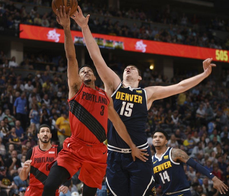 Portland Trail Blazers guard CJ McCollum, front left, drives to the rim past Denver Nuggets center Nikola Jokic in the second half of Game 7 of an NBA basketball second-round playoff series Sunday, May 12, 2019, in Denver. (AP Photo/John Leyba)