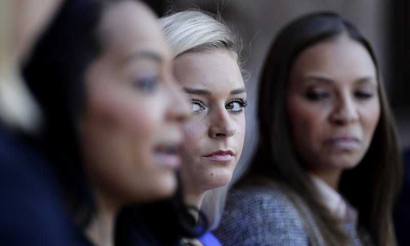 Former gymnast Amy Baumann, center, listens to former gymnast Tasha Schwikert during a news conference after they game testimony during a hearing about the statute of limitations child sex abuse victims have to sue their abusers, Monday, May 13, 2019, in Austin, Texas. (AP Photo/Eric Gay)