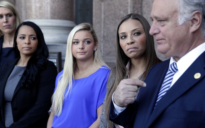 Former gymnasts, from left, Tasha Schwikert, Amy Baumann, and Jordan Schwikert listen Texas state Sen. (AP Photo/Eric Gay)