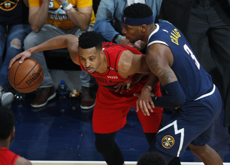 Portland Trail Blazers guard CJ McCollum, left, looks to pass the ball as Denver Nuggets forward Torrey Craig defends in the second half of Game 7 of an NBA basketball second-round playoff series Sunday, May 12, 2019, in Denver. (AP Photo/David Zalubowski)
