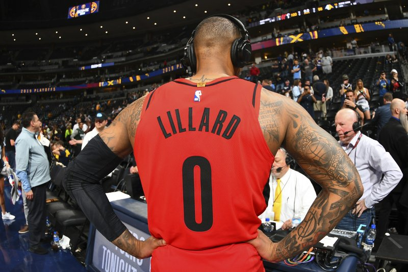 CORRECTS BYLINE IN SIGNOFF TO JOHN LEYBA NOT DAVID ZALUBOWSKI Portland Trail Blazers guard Damian Lillard talks to radio broadcasters after Game 7 of an NBA basketball second-round playoff series against the Denver Nuggets, Sunday, May 12, 2019, in Denver. (AP Photo/John Leyba)