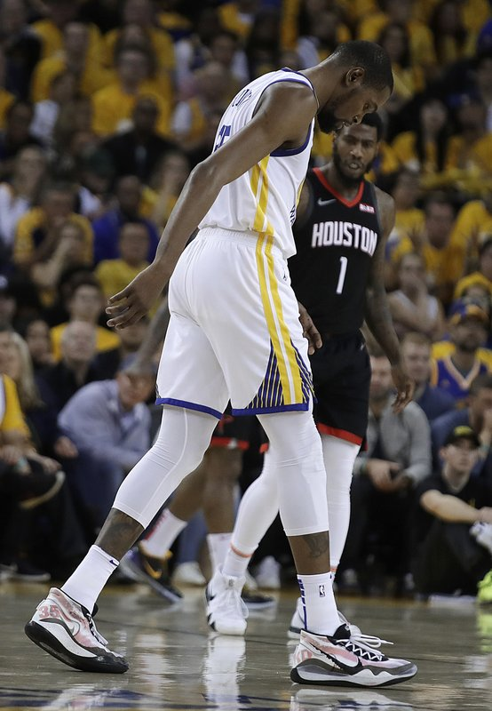 Golden State Warriors' Kevin Durant, center, limps off the court during the second half of Game 5 of the team's second-round NBA basketball playoff series against the Houston Rockets on Wednesday, May 8, 2019, in Oakland, Calif. (AP Photo/Ben Margot)