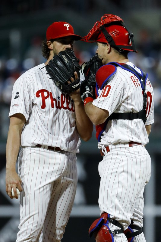 Philadelphia Phillies starting pitcher Aaron Nola, left, and catcher J.T. Realmuto talk during the first inning of a baseball game against the Milwaukee Brewers, Monday, May 13, 2019, in Philadelphia. (AP Photo/Matt Slocum)