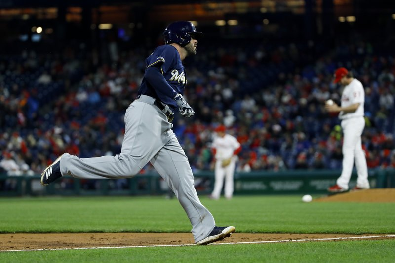 Milwaukee Brewers' Mike Moustakas, left, rounds the bases after hitting a home run off Philadelphia Phillies starting pitcher Aaron Nola, right, during the third inning of a baseball game, Monday, May 13, 2019, in Philadelphia. (AP Photo/Matt Slocum)