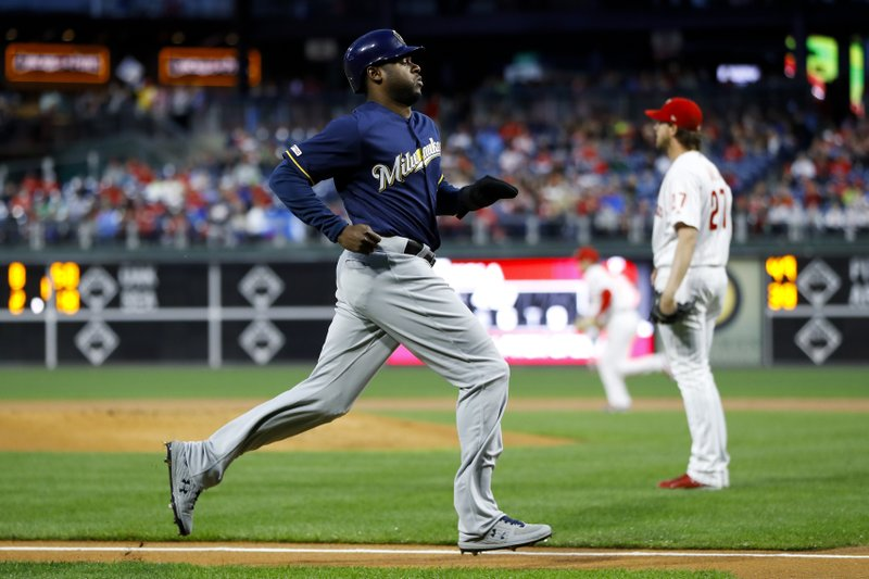 Milwaukee Brewers' Lorenzo Cain, left, runs past Philadelphia Phillies starting pitcher Aaron Nola to score on a double by Christian Yelich during the first inning of a baseball game, Monday, May 13, 2019, in Philadelphia. (AP Photo/Matt Slocum)