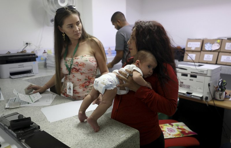 Arelys Pulido, right, holds her two-month-old daughter Zuleidys Antonella Primera as they are processed for her baby's birth certificate at the Erazmo Meoz hospital in Cucuta, on Colombia's border with Venezuela, Thursday, May 2, 2019. (AP Photo/Fernando Vergara)