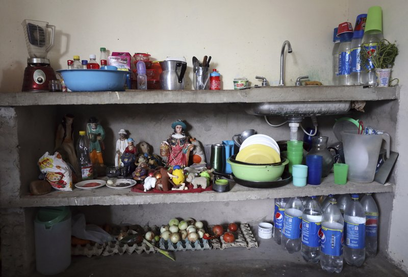 Vegetables, appliances, plates, cups, cutlery, toys and statuettes of popular saint stand in the kitchen of the Primera Pulido family in Cucuta, Colombia, Thursday, May 2, 2019. (AP Photo/Fernando Vergara)