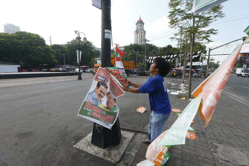 A Manila City public worker removes the campaign posters, mostly that of incumbent Mayor and former President Joseph