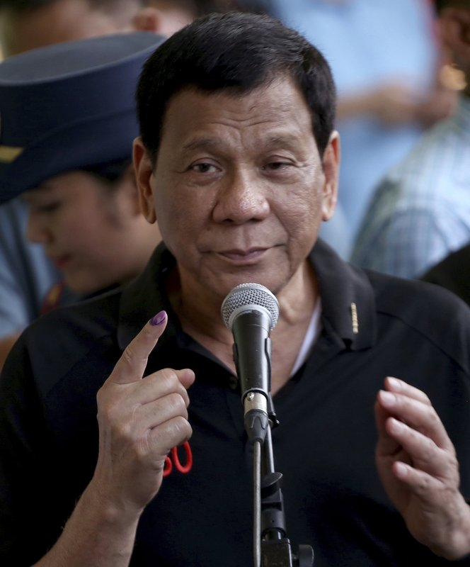 President Rodrigo Duterte shows his forefinger with an indelible ink to prove that he has voted for the country's midterm elections in his hometown of Davao city in southern Philippines Monday, May 13, 2019. (AP Photo/Manman Dejeto)
